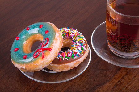 Donuts and cup of tea on wooden table Banco de Imagens