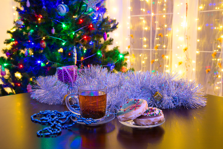 Donuts and cup of tea on Christmas background