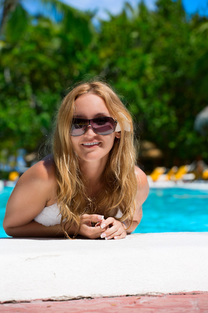 Smiling young woman relaxing in pool