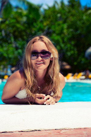 Smiling young woman relaxing in pool. toning