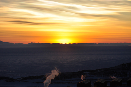 Sun setting over the ice shelf on ross island at Mcmurdo station