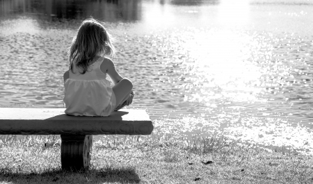 lonely child: Lonely little blonde girl sitting on wooden bench with space on side and watching ducks in pond