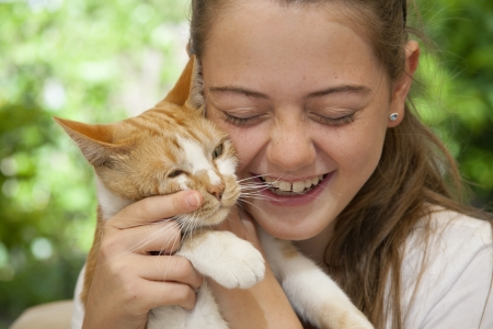 ginger cat: young girl holding her ginger cat