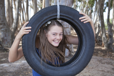 young girl playing with tyre swing photo