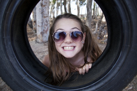 thrill: young girl playing with tyre swing