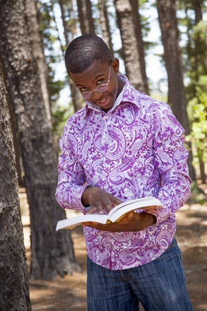 African  teenager boy reading a book outdoors in nature Stock Photo