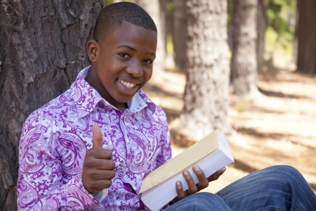 African  teenager boy reading a book outdoors in nature photo