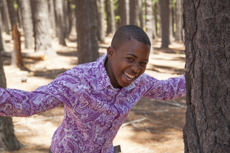 young african boy looking to the camera in the woods