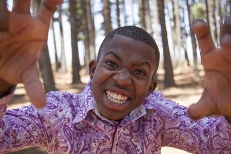 young african boy looking to the camera and pulling funny face in the woods Stock Photo