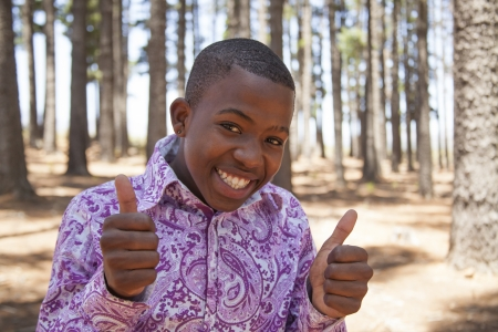 young african boy looking to the camera and smiling in the woods