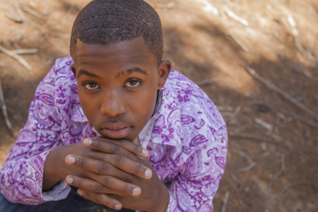 African boy sitting in the forest