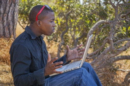 Smiling african student using a laptop outside photo