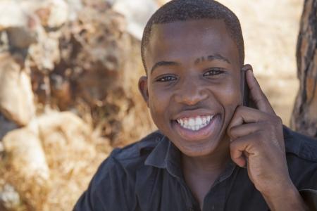 garcon africain: gar�on africain sur le t�l�phone portable � l'ext�rieur Banque d'images