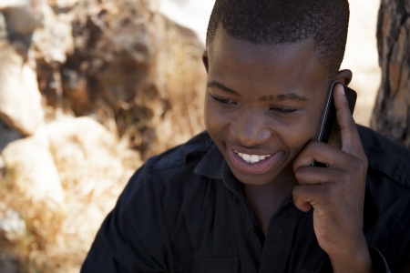 african boy on cell phone outside