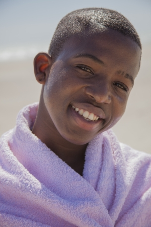 towel wrapped: attractive smiling boy at the beach with a towel wrapped around him Stock Photo