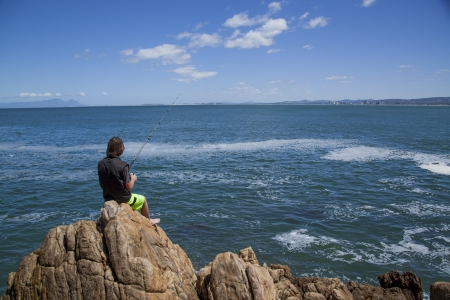 young teenage boy fishing by the sea on some rocks photo
