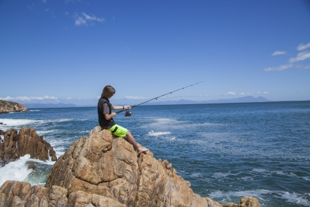 young teenage boy fishing by the sea on some rocks