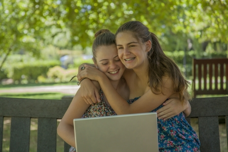 two girls with laptop outdoor sitting on a bench