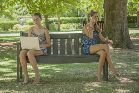 two girls with laptop and smart phone outdoor sitting on a bench photo