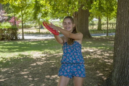 Young woman outdoor in a park tossing a flying pan