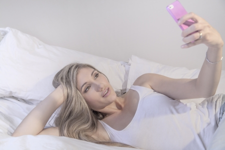young beautiful woman with phone on her bed Stock Photo
