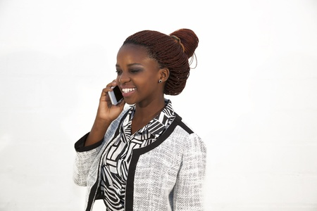 Young African woman on mobile phone against white Stock Photo