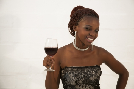 Beautiful young african woman holding a glass of red wine against white background