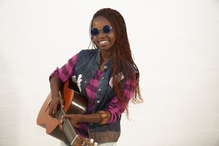 Beautiful african woman playing guitar against white background Stock Photo