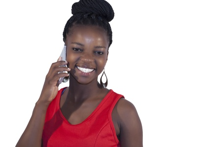 Young happy african woman talking into her cell phone on white background photo