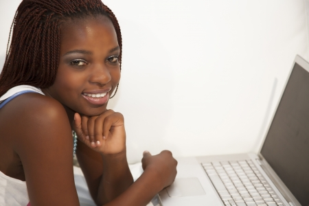 young african woman typing on computer laying on couch Stock Photo