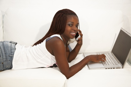 African teen working on laptop computer and talking on a cell phone; lying on a white couch Stock Photo