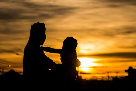 夕日を見て、彼女の子供を持つお母さんのシルエット。
