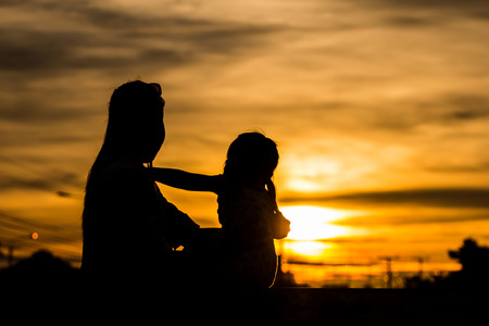 Silhouette of a mother holding her child, watching the sunset. Banco de Imagens