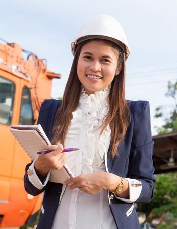 woman engineer: Beautiful young woman engineer wearing a helmet.