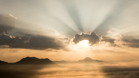 light rays: Sun shining behind the clouds on the mountain.