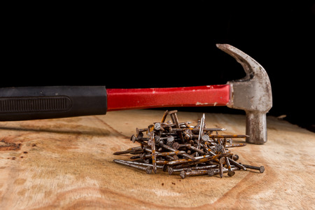 hammer head: Hammer head and nails on a wooden table.