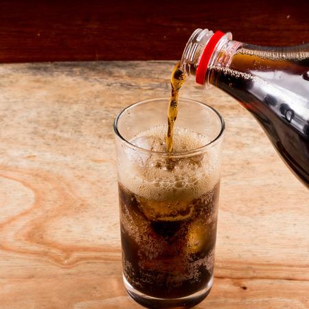 木製のテーブルにグラスにコーラを注ぐ。 写真素材