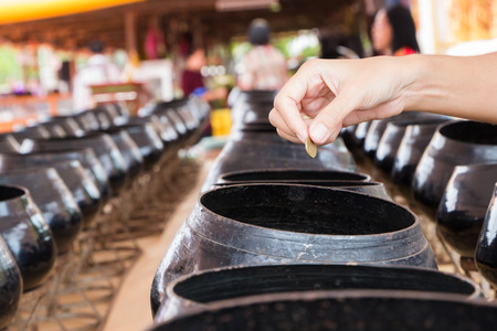 goodness: Hand put coin into small alms bowl, goodness belief in Buddhist religion. Stock Photo