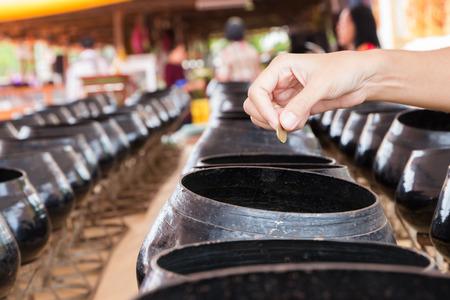 bondad: La mano puso la moneda en pequeño cuenco de las limosnas, la creencia en la bondad religión budista.