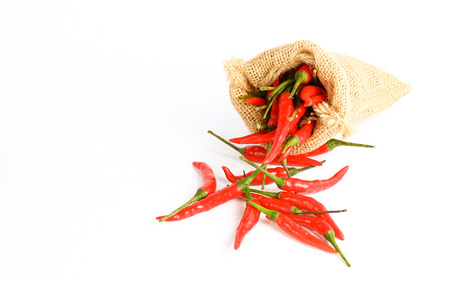 Red chili peppers in a sack bag on white background. photo