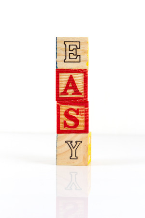 straightforward: Four wooden alphabet blocks on white background, stacked to form the word, easy.
