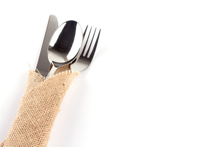 stacked up: spoon, fork and knife stacked up on a sackcloth. Stock Photo