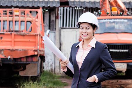 obrero trabajando: Ingeniero mujer hermosa celebración de planos en la mano, en el fondo con camiones.