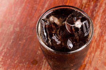 A glass of cola with ice on old wood textured