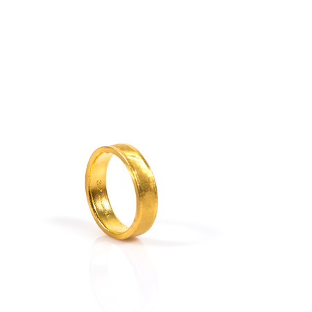 vows: Close up of golden wedding ring on white background. Stock Photo
