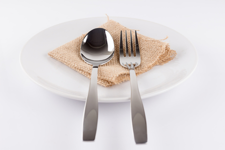 Spoon and fork on a plate on a white background. Stock Photo