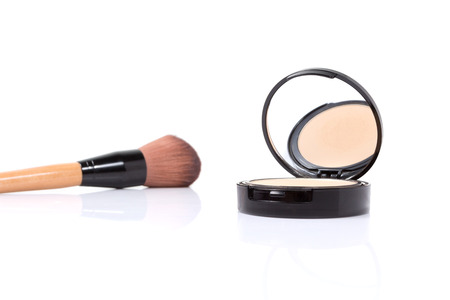 face powder: closeup of brush and face powder isolated on white background.