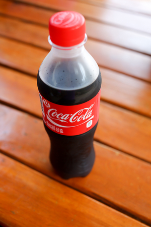 cola bottle: UDONTHANI, THAILAND - January 15, 2016. Coca Cola bottle on weathered wood. Coca Cola drinks are produced and manufactured by The Coca-Cola Company.
