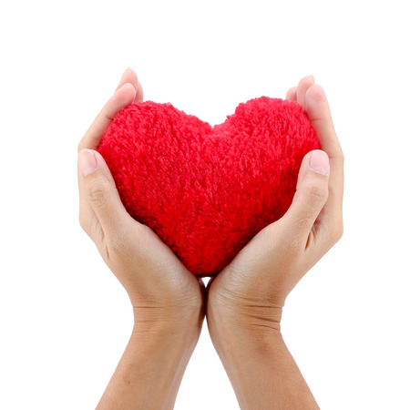 hands hold a red heart on white background.