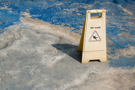 warns: A Caution Sign warns people of a wet floor at swimming pool Stock Photo